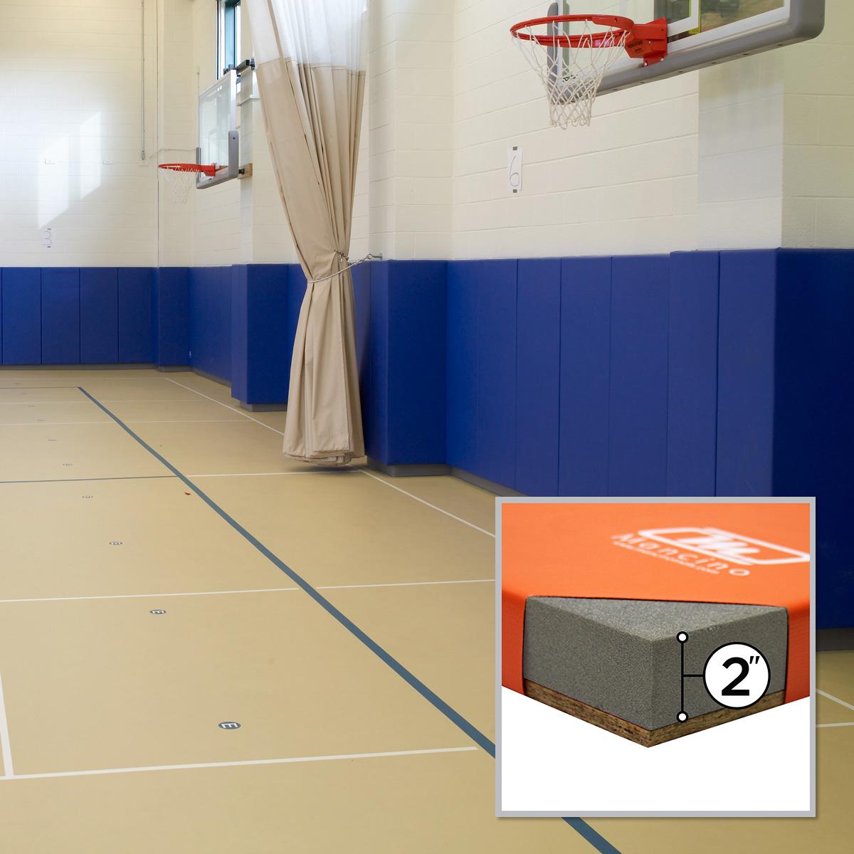 gymnasium with divider curtain and royal blue wall padding by mancino