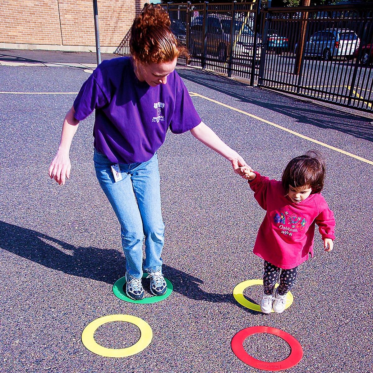 woman helping toddler walk through agility course set marker course