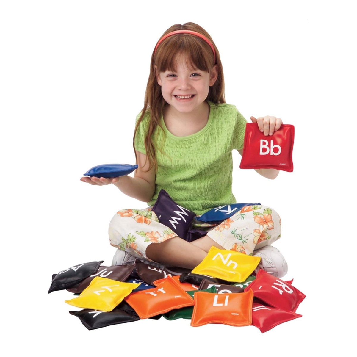 little girl with a set of colorful letters bean bags