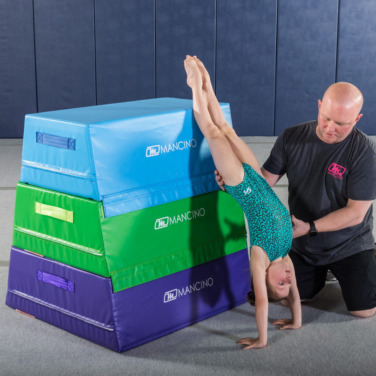 gymnastics coach training a student a handstand on a trapezoid training aid