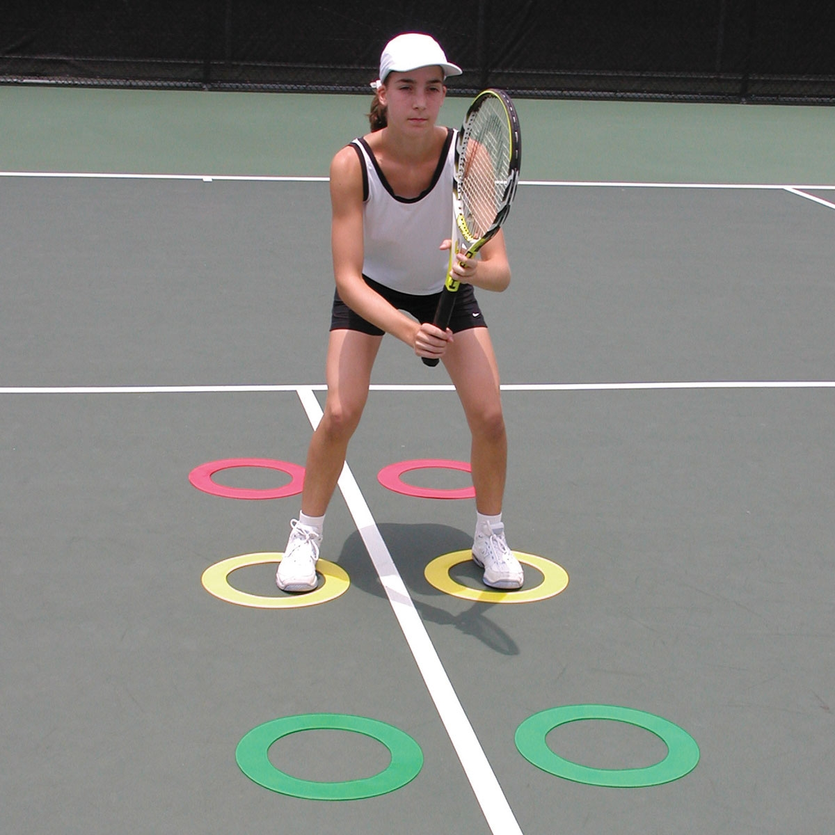 tennis play working on footing agility on tennis court with ring markers set