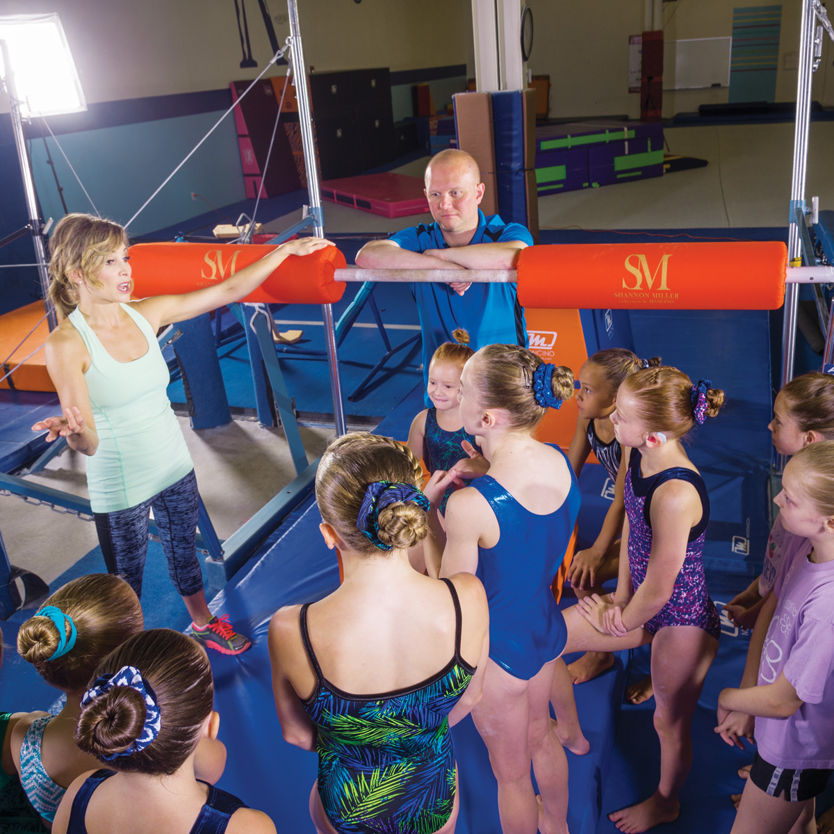 shannon miller instructing gymnasts uneven bar pads