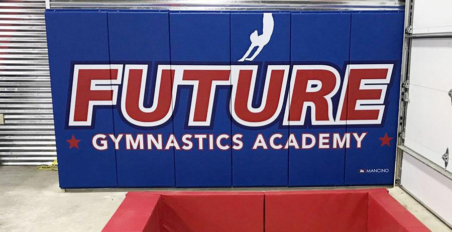 future gymnastics academy wall padding near in-ground pit